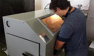 Utilizando la técnica del chorreado de arena en una cabina